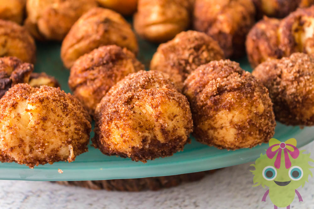 flaky dough balls covered in cinnamon and sugar on a teal plate