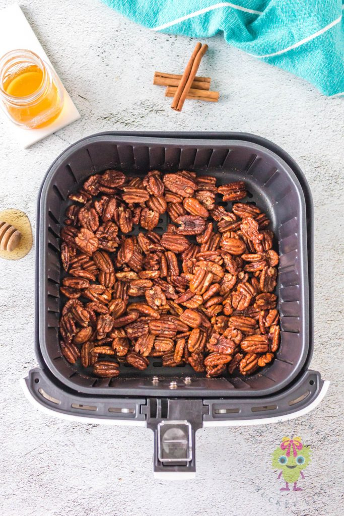 pecans in air fryer basket and honey and cinnamon sticks on top