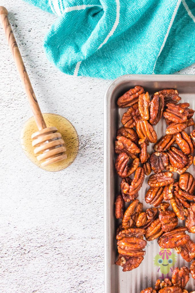 pecans on cookie sheet and honey dipper on table