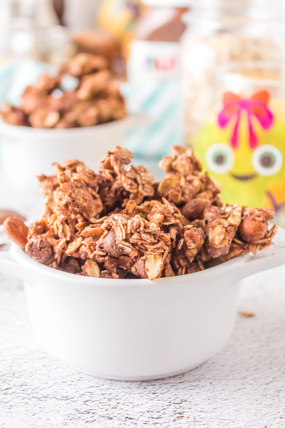 granola clusters in white bowl foreground and more granola in background