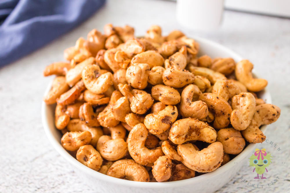 Roasted cashews in a white bowl center image