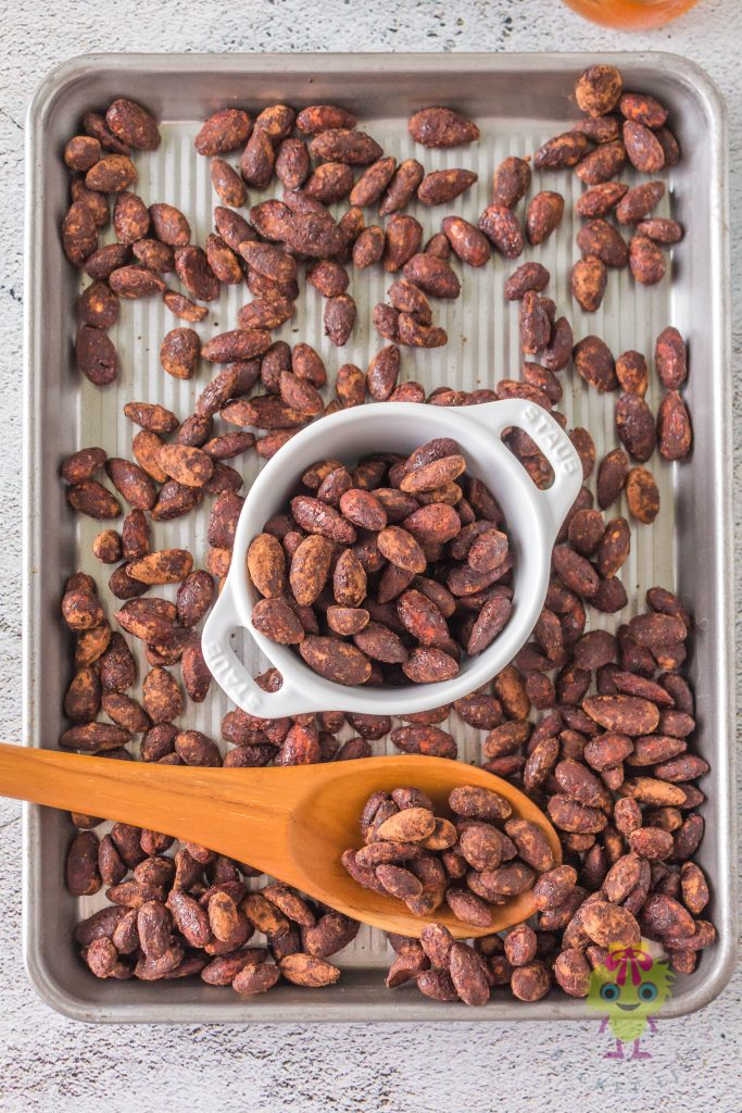 roasted almonds in a half cookie sheet and with a some almonds in a bowl center