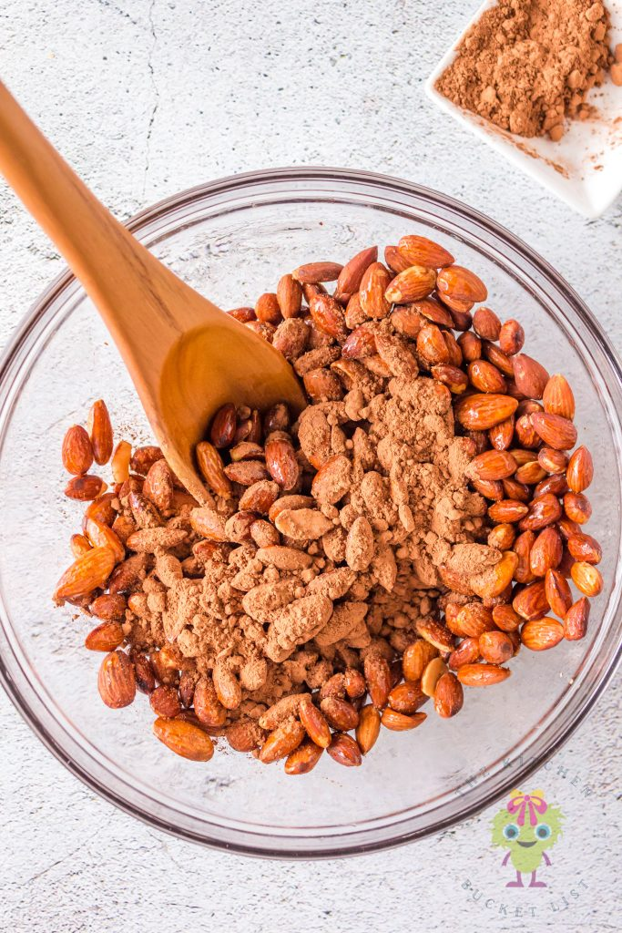 almonds with sprinkle cocoa powder over in a bowl