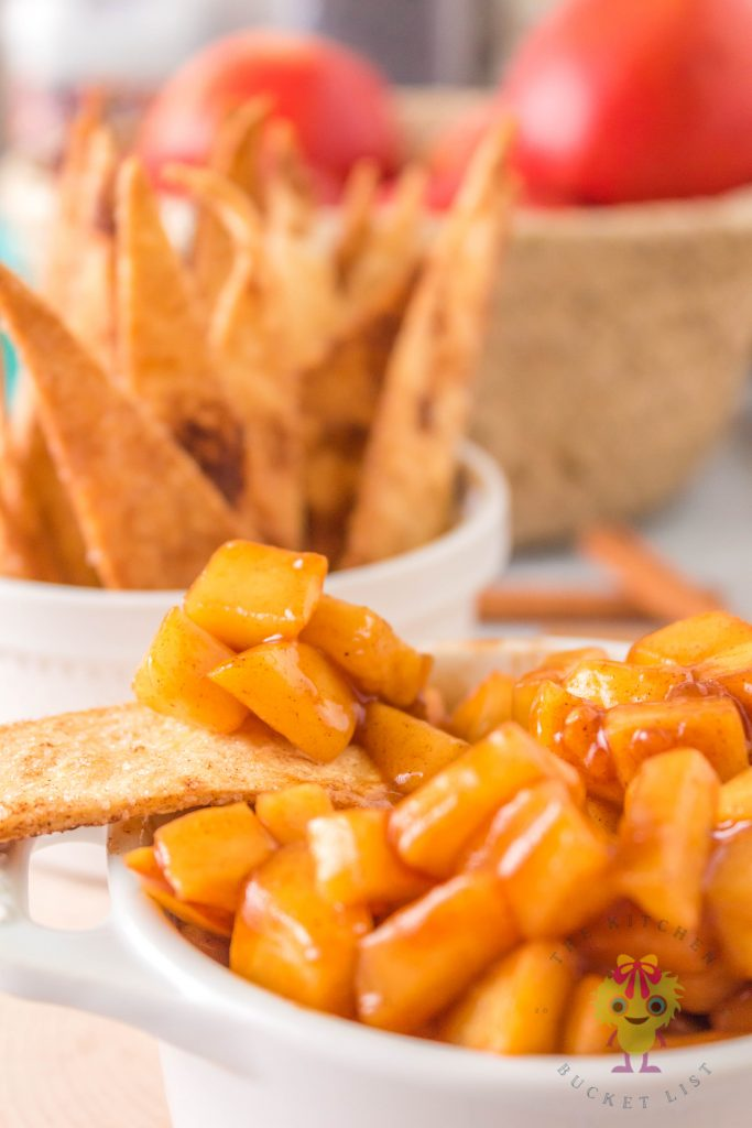 Apple dip on a tortilla chip with tortilla chips background and apples in basket