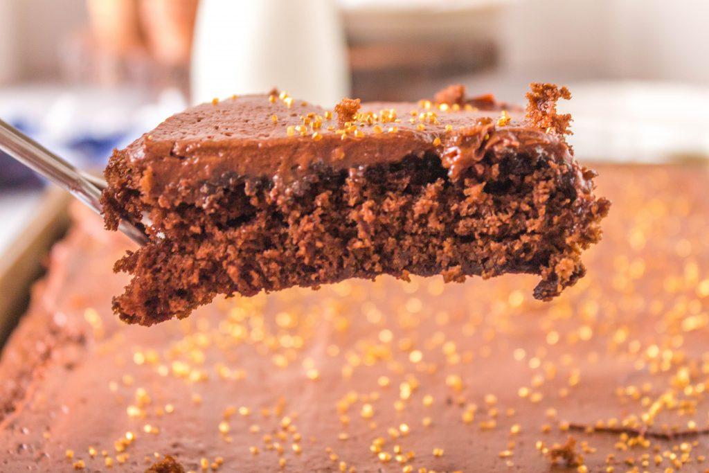slice of chocolate sheet pan cake in spatula above cake sheet