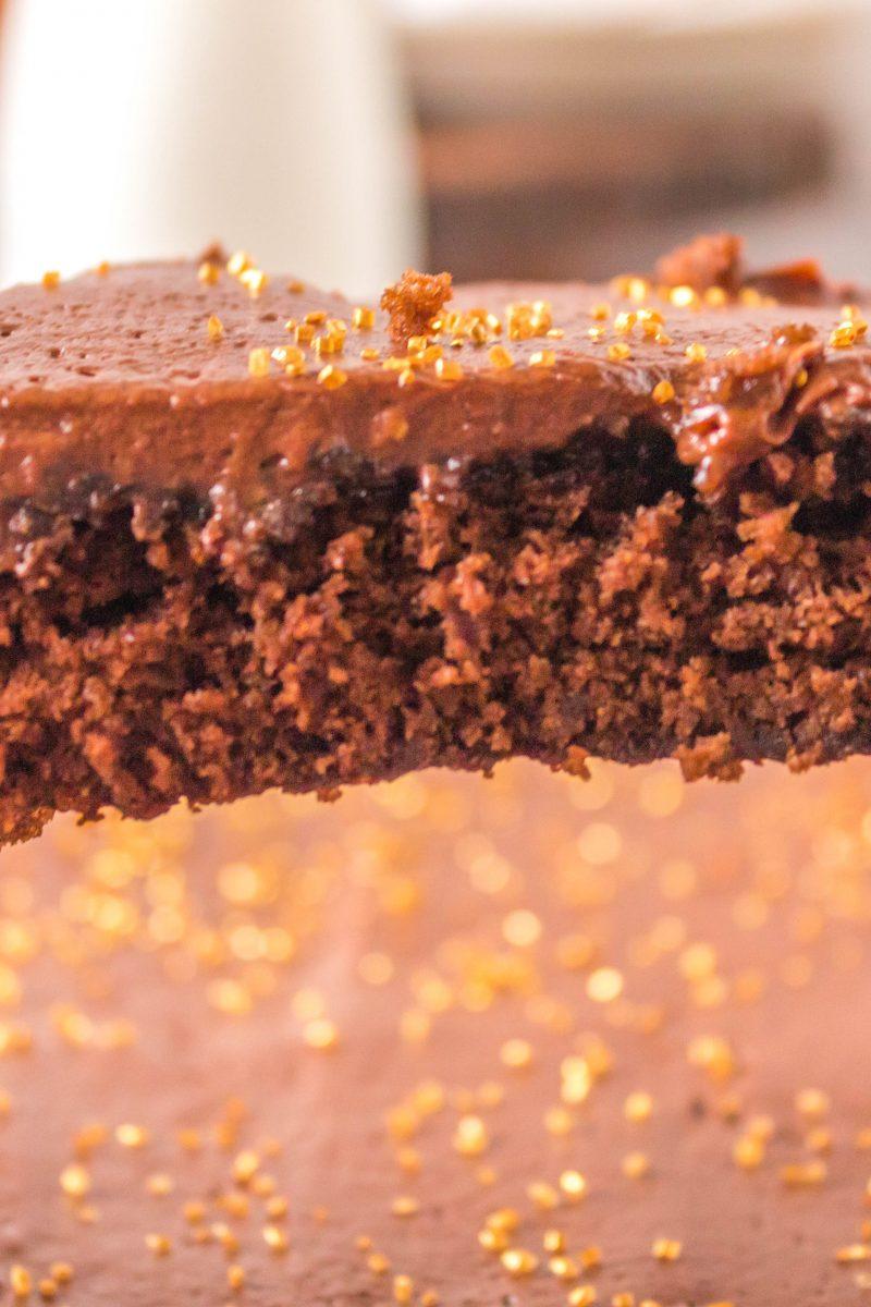slice of chocolate cake in spatula above cake sheet